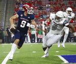Fresno State quarterback Jake Haener avoids a sack against UNLV linebacker Kylan Wilborn during the first half of an NCAA college football game in Fresno, Calif., Friday, Sept. 24, 2021. (AP Photo/Gary Kazanjian)
