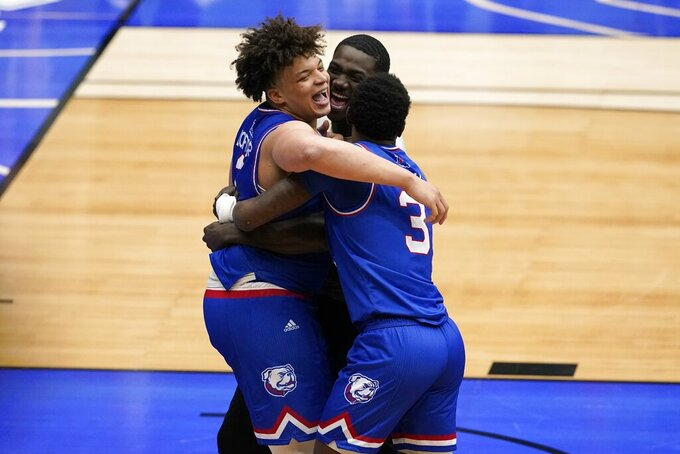 Louisiana Tech's Kenneth Lofton Jr., left, Amorie Archibald (3) and a member of the team, rear, celebrate their win in an NCAA college basketball game against Colorado State in the NIT, Sunday, March 28, 2021, in Frisco, Texas. (AP Photo/Tony Gutierrez)