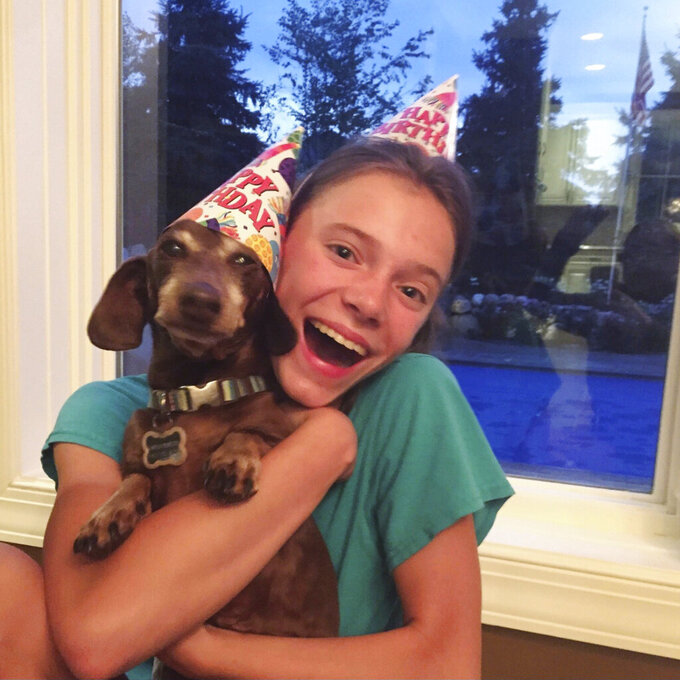 This August 2020 photo provided by Peyton Crest shows her with her dog at home in Minnetonka, Minn. The 18-year-old ays she developed anorexia before the pandemic but has relapsed twice since it began. ''It was my junior year, I was about to apply for college,'' Crest says. Suddenly deprived of friends and classmates, her support system, she'd spend all day alone in her room and became preoccupied with thoughts of food and anorexic behavior. (Courtesy Peyton Crest via AP)