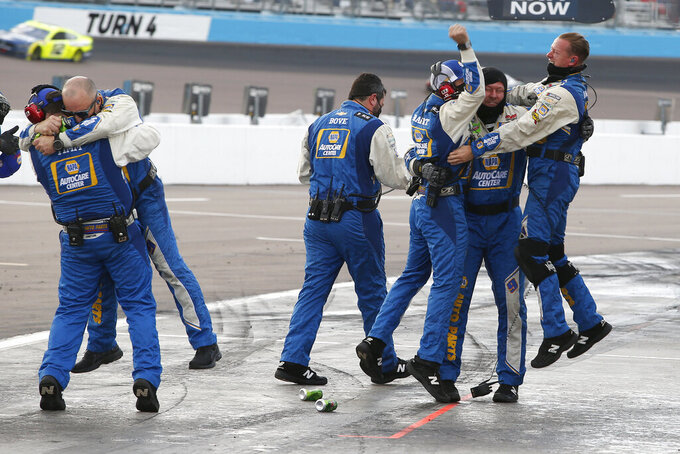 Chase Elliott's pit crew celebrate in their pit stall after winning the season championship and a NASCAR Cup Series auto race at Phoenix Raceway, Sunday, Nov. 8, 2020, in Avondale, Ariz. (AP Photo/Ralph Freso)