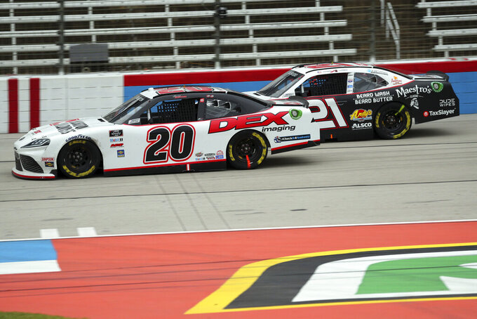 Harrison Burton (20) and Anthony Alfredo (21) come down the front stretch during a NASCAR Xfinity Series auto race at Texas Motor Speedway in Fort Worth, Texas, Saturday, Oct. 24, 2020. (AP Photo/Richard W. Rodriguez)