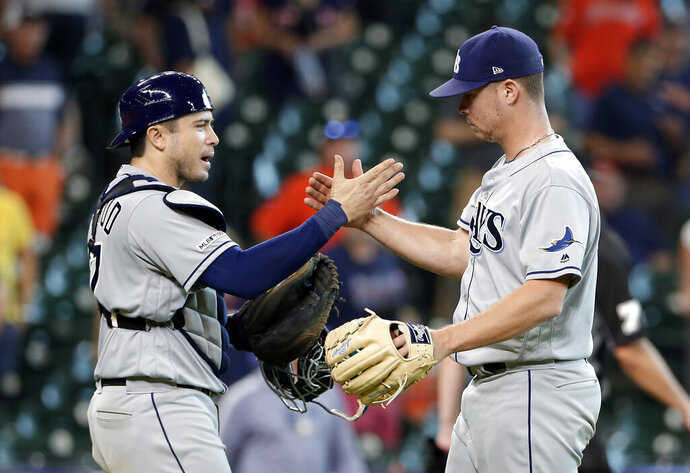 Tampa Bay Rays catcher Travis d'Arnaud, left, and closing pitcher Emilio Pagan, right, celebrate their win over the Houston Astros at the end of a baseball game Thursday, Aug. 29, 2019, in Houston. (AP Photo/Michael Wyke)