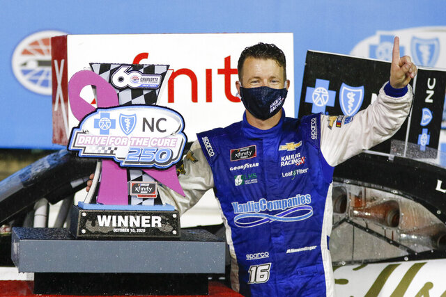 AJ Allmendinger stands beside his trophy after winning a NASCAR Xfinity Series auto race at Charlotte Motor Speedway in Concord, N.C., Saturday, Oct. 10, 2020. (AP Photo/Nell Redmond)