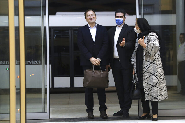Iranian doctor based in Florida Matteo Taerri, left, is welcomed by an Iranian Foreign Ministry official as his wife stands at right, upon arrival at Tehran's Imam Khomeini Airport from the U.S. after being part of a swap that saw a U.S. Navy veteran held by Iran return to America, Monday, June 8, 2020. Taerri, a dermatologist, had been charged with attempting to export a filter to Iran that he said was for vaccine research but that U.S. authorities said required a license because it could be used for chemical and biological warfare purposes. He was also accused of structuring a series of bank deposits below $10,000 to evade reporting requirements under federal law. (Majid Asgaripour/Mehr News Agency via AP)