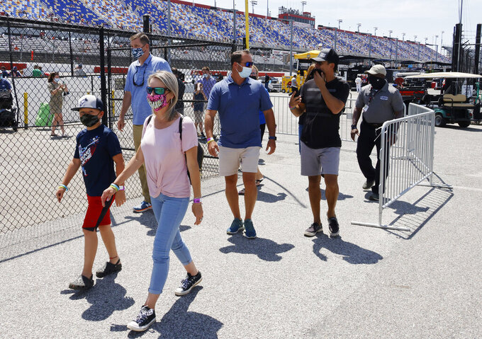 Fans walk through the garage area before a NASCAR Cup Series auto race at Darlington Raceway, Sunday, May 9, 2021, in Darlington, S.C. It is the first time this year that fans are allowed back in the garage area. (AP Photo/Terry Renna)