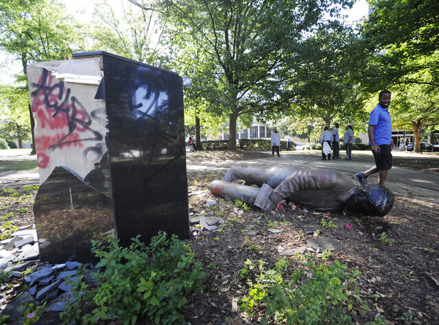 FILE - In this June 1, 2020 file photo, an unidentified man walks past a toppled statue of Charles Linn, a city founder who was in the Confederate Navy, in Birmingham, Ala., following a night of unrest. People shattered windows, set fires and damaged monuments in a downtown park after a protest against the death of George Floyd. Floyd died after being restrained by Minneapolis police officers on May 25. (AP Photo/Jay Reeves, File)