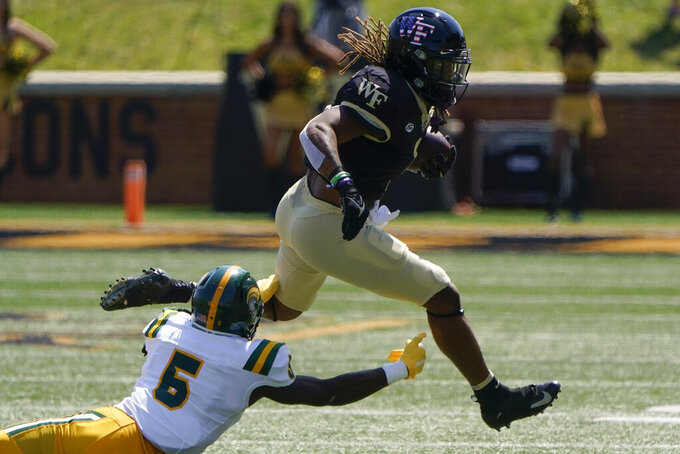 Wake Forest running back Christian Beal-Smith runs past Norfolk State's Devyn Coles during the first half of a NCAA college football game Saturday, Sept. 11, 2021, in Winston-Salem, N.C. (AP Photo/Chris Carlson)
