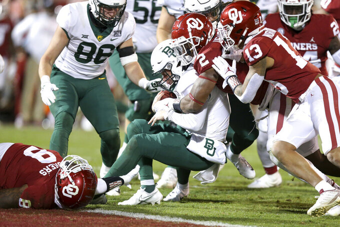 Oklahoma defensive lineman Perrion Winfrey (8), linebacker David Ugwoegbu (2) and defensive back Tre Norwood (13) tackle Baylor quarterback Charlie Brewer (5) during an NCAA college football game in Norman, Okla., Saturday, Dec. 5, 2020. (Ian Maule/Tulsa World via AP)