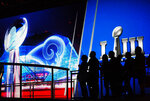 Fans line up in front of a big screen to have their photo taken with the Vince Lombardi Trophy on display at the NFL Experience ahead of Sunday's Super Bowl 53 football game between the Los Angeles Rams and New England Patriots in Atlanta, Wednesday, Jan. 30, 2019. (AP Photo/David Goldman)