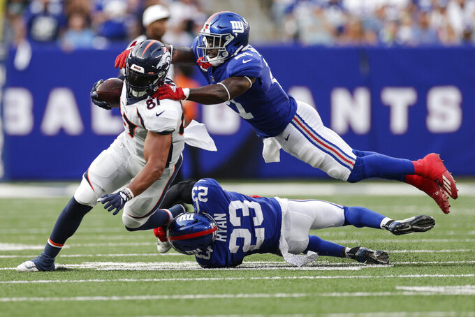 New York Giants' Logan Ryan (23) and Jabrill Peppers (21) tackle Denver Broncos' Noah Fant (87) during the second half of an NFL football game Sunday, Sept. 12, 2021, in East Rutherford, N.J. (AP Photo/Adam Hunger)