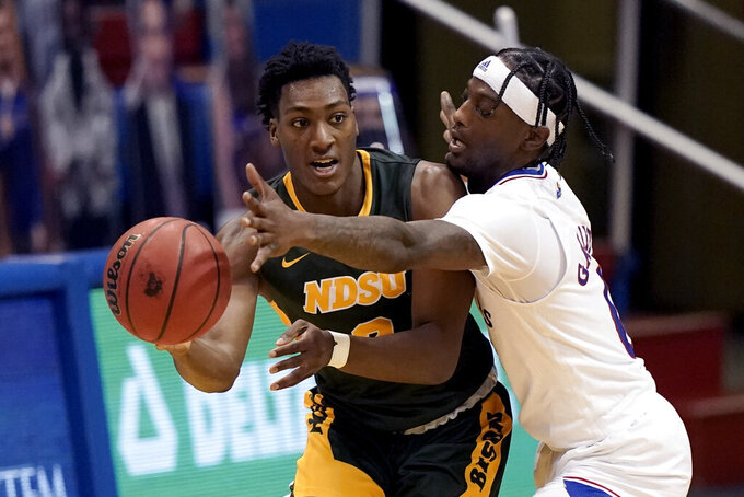 North Dakota State's Tyree Eady passes the ball around Kansas' Marcus Garrett during the second half of an NCAA college basketball game Saturday, Dec. 5, 2020, in Lawrence, Kan. Kansas won 65-61. (AP Photo/Charlie Riedel)
