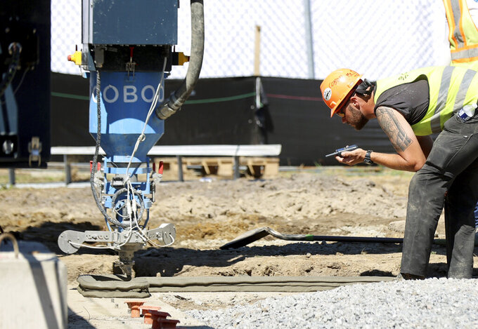 Concrete is laid as a 3d printed house that is being built in Midlothian, Va., on Thursday, June 24, 2021. This house is for a first time or single dwelling buyer who is interested in owning their own home. (Daniel Sangjib Min/Richmond Times-Dispatch via AP)