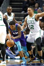 Charlotte Hornets' Malik Monk (1) dribbles away from Boston Celtics' Kemba Walker, left and Grant Williams, right, during the first half of an NBA basketball game in Charlotte, N.C., Thursday, Nov. 7, 2019. (AP Photo/Bob Leverone)