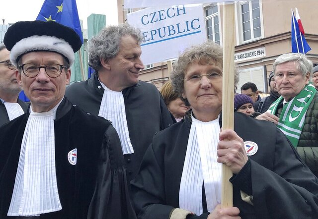Judges from Italy, the Netherlands and elsewhere in Europe, many wearing their professional gowns, take part in a march in support of judicial independence in Warsaw, Poland, on Saturday Jan. 11, 2020. The judges marched silently in Warsaw in a show of solidarity with Polish peers who are protesting a bill that would allow the government to fire judges who issue rulings officials don't like. (AP Photo/Vanessa Gera)
