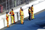 Ryan Newman's crew stands near a wall on pit road as they are kept back from rescue workers that are aiding Newman after he was involved in a crash on the final lap of the NASCAR Daytona 500 auto race at Daytona International Speedway, Monday, Feb. 17, 2020, in Daytona Beach, Fla. Sunday's race was postponed because of rain. (AP Photo/David Graham)