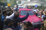 Supporters of Pakistan's ailing former prime minister Nawaz Sharif surround his vehicle at the airport in Lahore, Pakistan, Tuesday, Nov. 19, 2019. Sharif has arrived to board a special plane after a court permitted him to leave the country for four weeks abroad for medical treatment. (AP Photo/K.M. Chaudary)