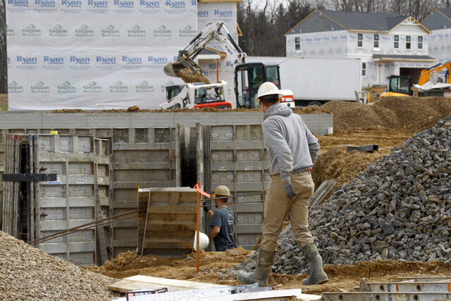In this March 18 ,2020 photo, construction continues at a housing plan in Zelienople, Pa. Spending on U.S. construction projects fell 1.3% in February with housing and nonresidential construction both showing weakness even before the coronavirus struck with force in the United States. The Commerce Department said the February decline followed a 2.8% rise in construction in January.  (AP Photo/Keith Srakocic)