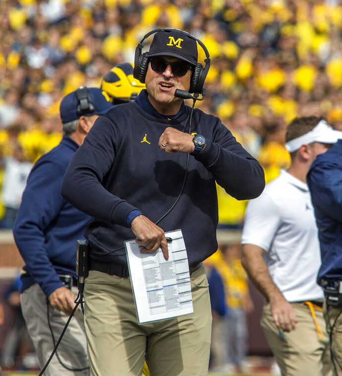 Michigan head coach Jim Harbaugh signals to game officials from the sideline in the second quarter of an NCAA college football game against Iowa in Ann Arbor, Mich., Saturday, Oct. 5, 2019. (AP Photo/Tony Ding)