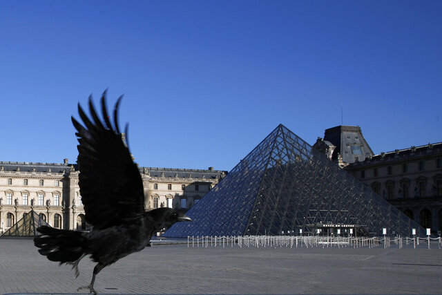 FILE - In this Monday, March 30, 2020 file photo, a black crow flies over in the deserted Louvre museum courtyard in Paris. The European Union unveiled Wednesday May 13, 2020, its plan to help confinement-tortured citizens across the 27 nations salvage their summer vacations after months of coronavirus lockdown and resurrect Europe's badly battered tourism industry. (AP Photo/Francois Mori, File)