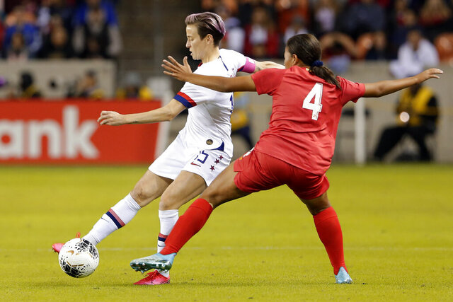 U.S. forward Megan Rapinoe (15) moves the ball under pressure from Panama defender Hilary Jaen (4) during the first half of a CONCACAF women's Olympic qualifying soccer match Friday, Jan. 31, 2020, in Houston. (AP Photo/Michael Wyke)