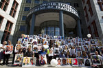 Demonstrators hold pictures of the plane crash victims during a vigil on the six-month anniversary of the crash of a Boeing 737 Max 8, killing 157 people, in Ethiopia on March 10, which has resulted in the grounding hundreds of the planes worldwide, outside of the Department of Transportation, Tuesday, Sept. 10, 2019 in Washington. (AP Photo/Jose Luis Magana)