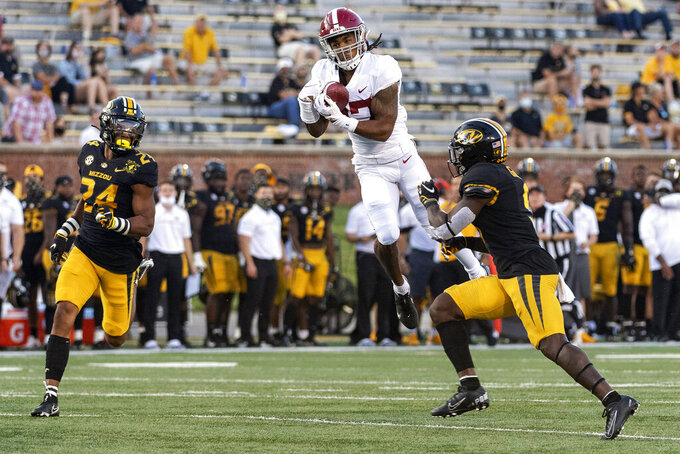 FILE - In this Saturday, Sept. 26, 2020, file photo, Alabama wide receiver Jaylen Waddle, center, pulls down a reception between Missouri's Tyree Gillespie, right, and Ishmael Burdine, left, during the first quarter of an NCAA college football game in Columbia, Mo.  No. 2 Alabama doesn't look like a team that lost quarterback Tua Tagovailoa and two first-round receivers. Quarterback Mac Jones still has a selection of some of the SEC's best playmakers, including Jaylen Waddle. (AP Photo/L.G. Patterson, File)