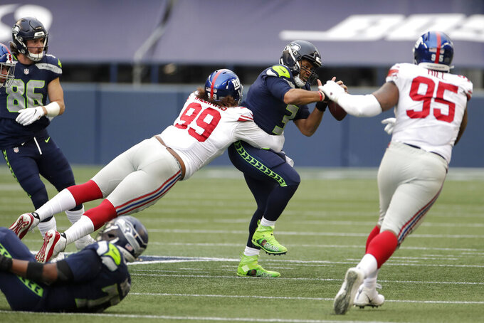 Seattle Seahawks quarterback Russell Wilson, center, is sacked by New York Giants defensive end Leonard Williams (99) during the second half of an NFL football game, Sunday, Dec. 6, 2020, in Seattle. The Giants won 17-12. (AP Photo/Larry Maurer)