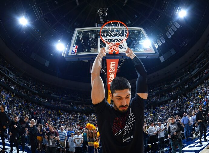 Portland Trail Blazers center Enes Kanter hangs on the net before the first half of Game 7 of an NBA basketball second-round playoff series against the Denver Nuggets Sunday, May 12, 2019, in Denver. (AP Photo/John Leyba)