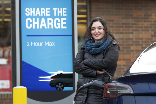 In this Friday, Dec. 20, 2019, photo, Neda Deylami poses for a portrait while charging her electric vehicle at a Chicago area grocery store. Owners of electric vehicles in a number of states will start seeing fees to pay for road repairs in the new year. At least eight states will begin charging new or higher registration fees Wednesday, Dec. 25, for electric vehicles or plug-in hybrids.