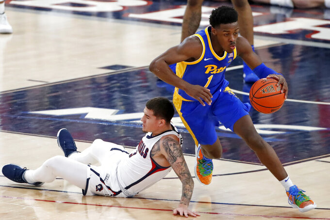 Pittsburgh's Xavier Johnson (1) dribbles around Robert Morris' Dante Treacy during the first half of an NCAA college basketball game in Pittsburgh, Tuesday, Nov. 12, 2019. (AP Photo/Gene J. Puskar)