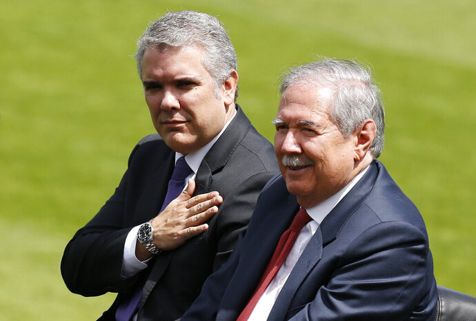 FILE - In this Dec. 17, 2018 file photo, Colombia's President Ivan Duque places his hand over his chest as he reviews the troops with Defense Minister Guillermo Botero during a swearing-in ceremony for the new military and police commanders, in Bogota, Colombia. Botero has on Wednesday, Nov. 6, 2019, tendered his resignation as the country's defense minister. (AP Photo/Fernando Vergara, File)