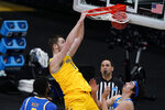 Michigan center Hunter Dickinson (1) dunks the ball over UCLA forward Cody Riley, left, and guard Jaime Jaquez Jr., right, during the first half of an Elite 8 game in the NCAA men's college basketball tournament at Lucas Oil Stadium, Tuesday, March 30, 2021, in Indianapolis. (AP Photo/Michael Conroy)