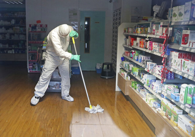 A man in protective clothing cleans the County Oak Medical Centre GP practice which has been temporarily closed