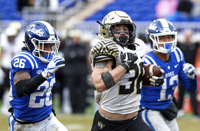 Wake Forest's Cade Carney (36) rushes past Duke's Troy Duncan (26) and Jordan Hayes (13) during the second half of an NCAA college football game in Durham, N.C., Saturday, Nov. 24, 2018. (AP Photo/Ben McKeown)