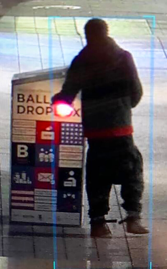 """This surveillance image provided by the Boston Police Department shows a man approaching a ballot drop box outside the Boston Public Library, early Sunday, Oct. 25, 2020, in downtown Boston. Massachusetts election officials say a fire was set at the ballot drop box holding more than 120 ballots in what appears to have been a """"deliberate attack."""