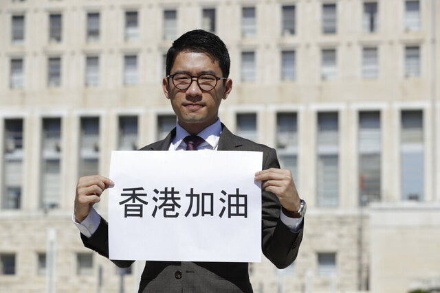 Hong Kong activist Nathan Law holds a banner reading in Chinese