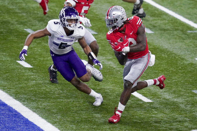 FILE - In this Dec. 19, 2020, file photo, Ohio State running back Trey Sermon, right, scores past Northwestern defensive back JR Pace (5) during the second half of the Big Ten championship NCAA college football game in Indianapolis. The proposed 12-team College Football Playoff will make winning a conference more important than ever before, with six spots reserved for league champions. (AP Photo/Darron Cummings, File)