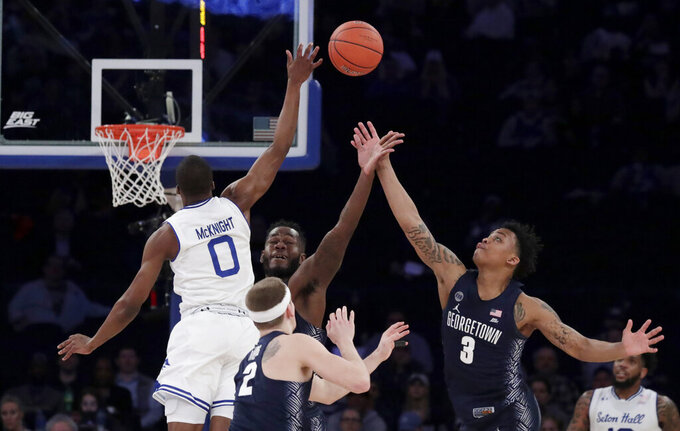 Seton Hall guard Quincy McKnight (0) competes for the ball against Georgetown guard Mac McClung (2), guard James Akinjo (3) and center Jessie Govan during the second half of an NCAA college basketball game in the Big East men's tournament, Thursday, March 14, 2019, in New York. Seton Hall won 73-57. (AP Photo/Julio Cortez)