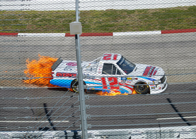 The truck of Gus Dean catches fire during the NASCAR Gander Outdoors Truck Series race at Martinsville Speedway in Martinsville, Va. Saturday, March 23, 2019. (AP Photo/Matt Bell)