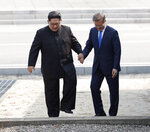 FILE - In this April 27, 2018, file photo, North Korean leader Kim Jong Un, left, and South Korean President Moon Jae-in cross the border line at the border village of Panmunjom in Demilitarized Zone. Kim's threat to show the world a new strategic weapon and possibly resume long-range missile tests is another dramatic turn in his high-stakes summitry with President Donald Trump. (Korea Summit Press Pool via AP, File)