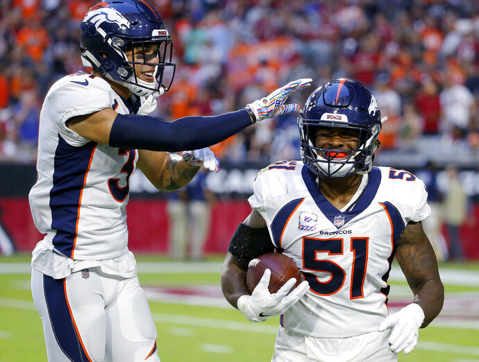 FILE - In this Oct. 18, 2018, file photo, Denver Broncos linebacker Todd Davis (51) celebrates his interception for a touchdown with free safety Justin Simmons during the first half of an NFL football game against the Arizona Cardinals in Glendale, Ariz. Davis practiced Wednesday, Sept. 11, for the first time since tearing his left calf on the first day of training camp July 18. Davis, who was the team's leading tackler last season, said he hopes to play Sunday against the Chicago Bears. (AP Photo/Rick Scuteri, File)