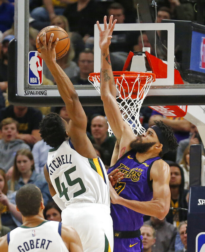 Utah Jazz guard Donovan Mitchell (45) dunks on Los Angeles Lakers center JaVale McGee (7) during the first half of an NBA basketball game Friday, Jan. 11, 2019, in Salt Lake City. (AP Photo/Rick Bowmer)