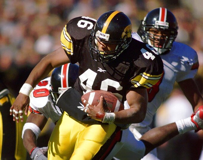 FILE - Iowa running back Ladell Betts breaks a tackle by Indiana's Greg Yeldell, background left, during a 29-yard touchdown run in the second quarter in Iowa City, Iowa, in this Saturday, Oct. 23, 1999, file photo. Ladell Betts will return to Iowa to coach running backs and George Barnett has been hired to coach the Hawkeyes' offensive line, coach Kirk Ferentz announced Monday, March 15, 2021. (AP Photo/Charlie Neibergall, File)