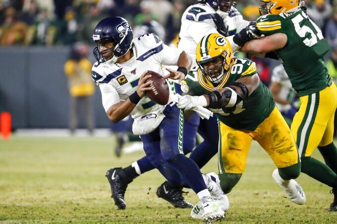 Seattle Seahawks' Russell Wilson tries to get away from Green Bay Packers' Kenny Clark during the first half of an NFL divisional playoff football game Sunday, Jan. 12, 2020, in Green Bay, Wis. (AP Photo/Matt Ludtke)
