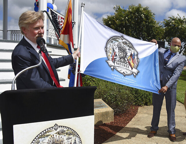New Natchez, Miss., Mayor Dan Gibson, left, presents a flag to outgoing Mayor Darryl Grennell, Friday, July 24, 2020. The flag features the official seal of the City of Natchez. Gibson hopes to have the flag adopted as the new city flag. (Ben Hillyer/The Natchez Democrat via AP)