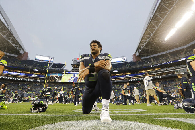Seattle Seahawks quarterback Russell Wilson kneels on the field as he stretches before an NFL football preseason game against the Oakland Raiders, Thursday, Aug. 29, 2019, in Seattle. (AP Photo/Elaine Thompson)