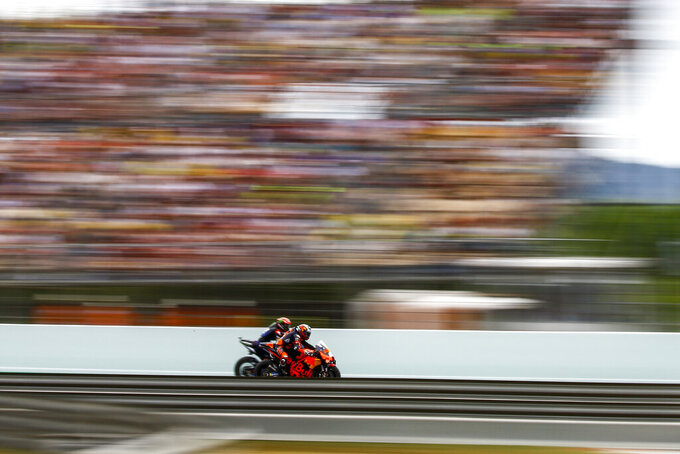 Portugal's Miguel Oliveira of KTM, right, on his way to win the Catalunya Motorcycle Grand Prix at the Barcelona Catalunya racetrack in Montmelo, near Barcelona, Spain, Sunday, June 6, 2021. (AP Photo/Joan Monfort)