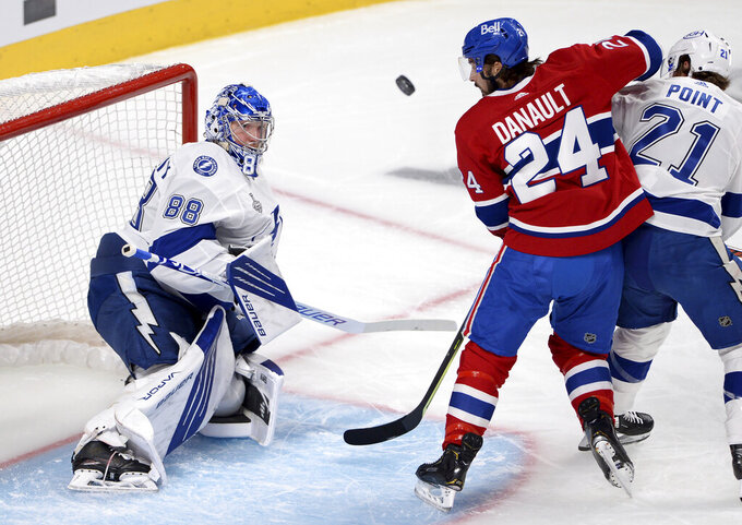 Tampa Bay Lightning's goaltender Andrei Vasilevskiy (88) makes a save as teammate Brayden Point (21) and Montreal Canadiens' Phillip Danault (24) tussle outside the crease during the first period of Game 4 of the NHL hockey Stanley Cup final in Montreal, Monday, July 5, 2021. (Ryan Remiorz/The Canadian Press via AP)