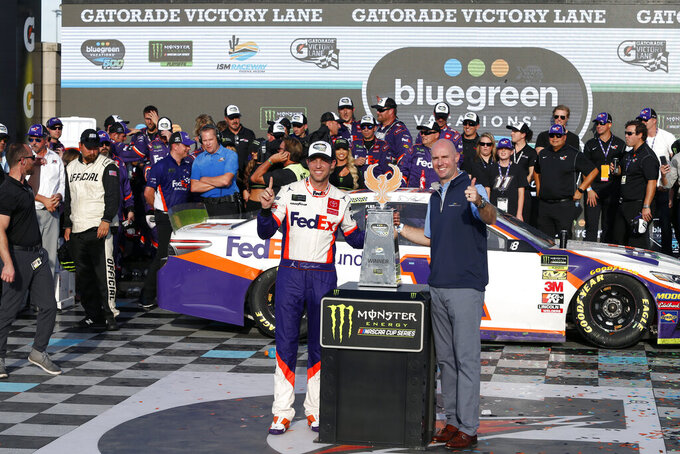 Denny Hamlin, left, and Shawn Pearson, President and CEO of Bluegreen Vacations, stand with the winners trophy in victory lane following the NASCAR Cup Series auto race at ISM Raceway, Sunday, Nov. 10, 2019, in Avondale, Ariz. (AP Photo/Ralph Freso)