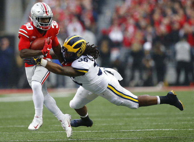 Michigan linebacker Devin Gil, right, tackles Ohio State running back Demario McCall during the first half of an NCAA college football game Saturday, Nov. 24, 2018, in Columbus, Ohio. (AP Photo/Jay LaPrete)
